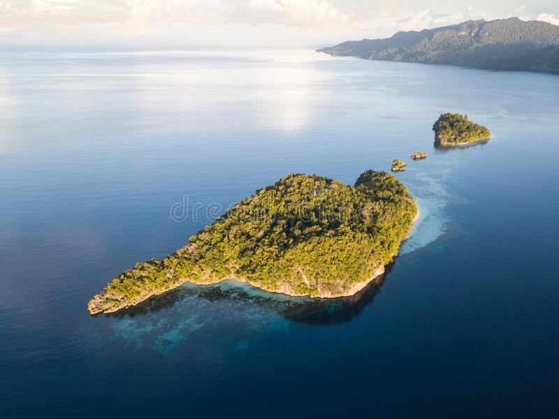 Aerial View of Remote Islands in Raja Ampat. The amazing limestone islands found in Raja Ampat, Indonesia, are surrounded by healthy coral reefs. This remote royalty free stock photos