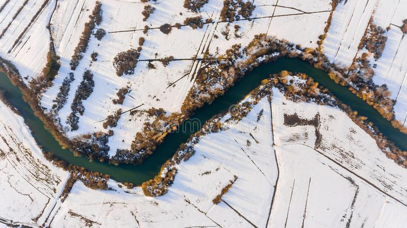 Aerial view riverbend passing snow covered fields. royalty free stock photography