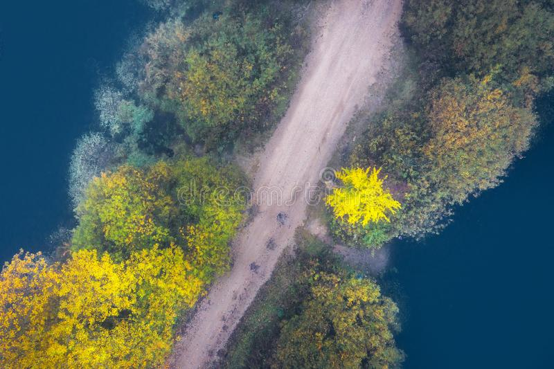 Aerial view on road with autumn trees through blue lake. Road crossing lake. Fall nature royalty free stock images