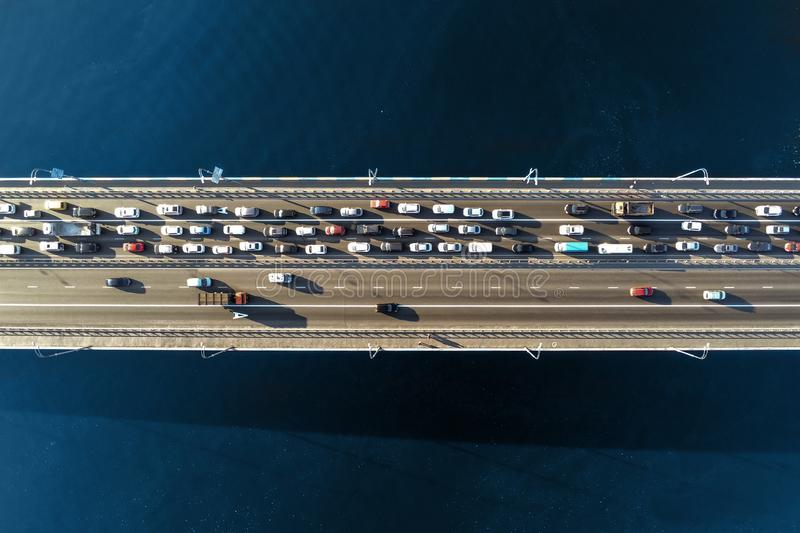 Aerial view of road bridge across river with heavy traffic jam in one direction. Rush hour with mash and overloading of road infra royalty free stock photos