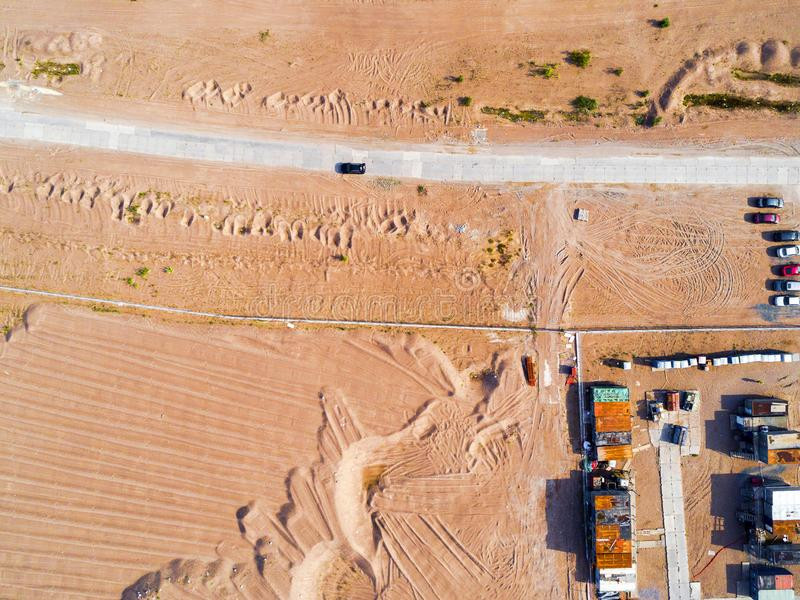 Aerial view of road with car. Aerial view of a country road with moving car and sand. Car passing by. Aerial construction road. Ae. Rial view flying. Captured stock images