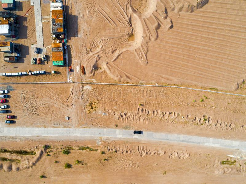 Aerial view of road with car. Aerial view of a country road with moving car and sand. Car passing by. Aerial construction road. Ae. Rial view flying. Captured royalty free stock images