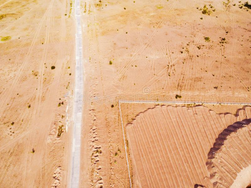 Aerial view of road with. Aerial view of a country road with sand. Car passing by. Aerial construction road. Aerial view flying. C. Aptured from above with a royalty free stock photography