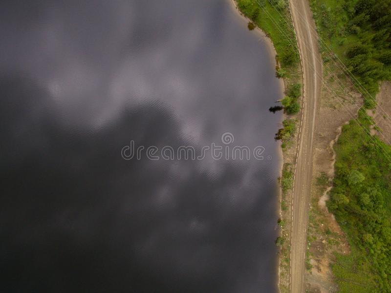 Aerial view of road between green summer forest and blue river stock image