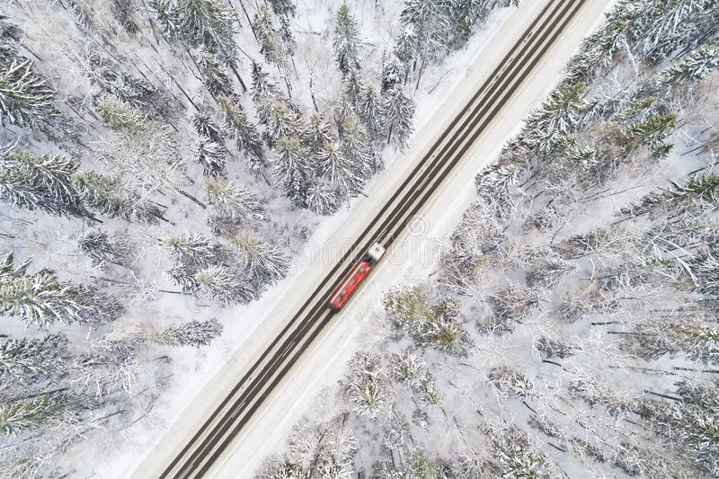 Aerial view of road with red truck in winter forest. Aerial view of snow covered road in winter forest, truck passing by, motion blur stock images
