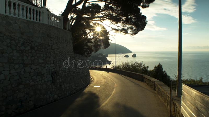 Aerial view on road by the sea and dramatic sky with sunset, lonely rock background. Shot. Sunset over the Highway in royalty free stock photography
