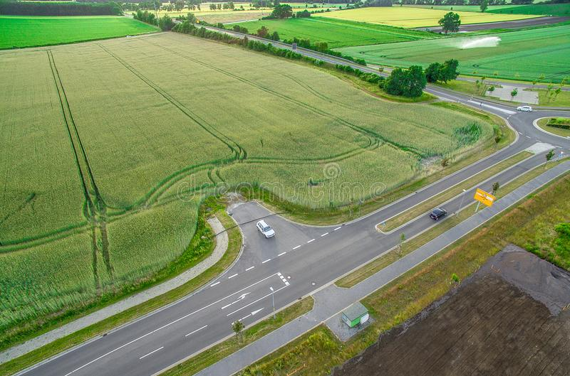 Aerial view of a road with signs and guidelines for traffic between a new development area for an industrial estate and an arable. Area with green wheat royalty free stock photo