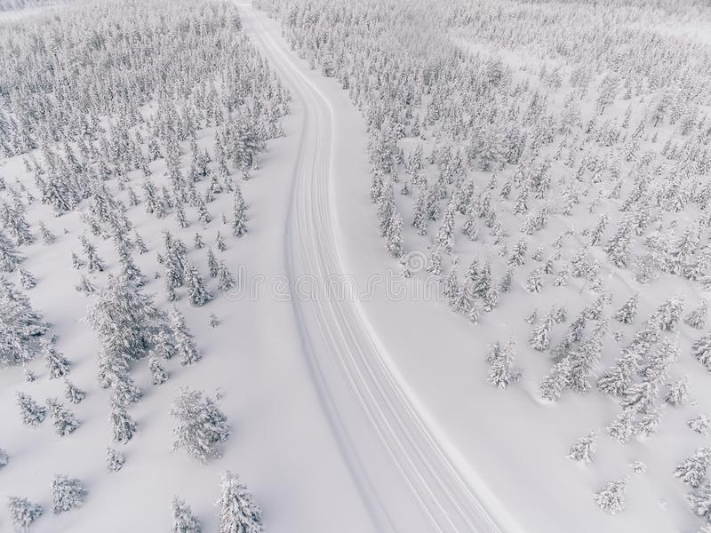 Aerial view of the road in the winter snow forest in Finland royalty free stock image