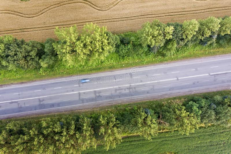 Aerial view of a road between yellow wheat fields and green trees.  stock photography