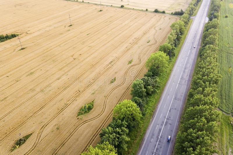 Aerial view of a road between yellow wheat fields and green trees.  royalty free stock photos