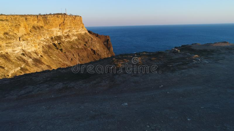 Aerial view of rock cliff and the surrounding sea water in sunset sky. Shot. Steep slope of mountain near the calm sea stock images