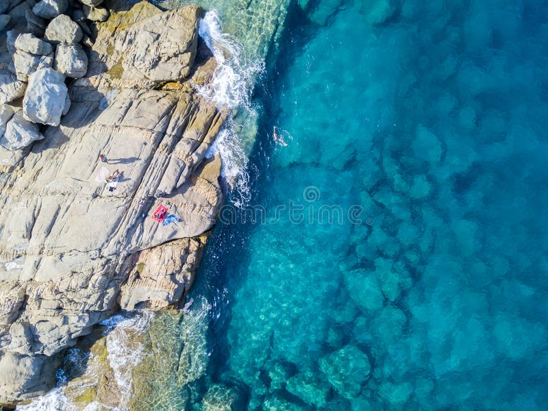 Aerial view of rocks on the sea. Swimmers, bathers floating on the water. People sunbathing on the towel. Aerial view of rocks on the sea. Overview of seabed royalty free stock photo