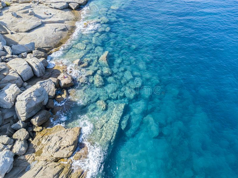 Aerial view of rocks on the sea. Swimmers, bathers floating on the water. People sunbathing on the towel. Aerial view of rocks on the sea. Overview of seabed royalty free stock image