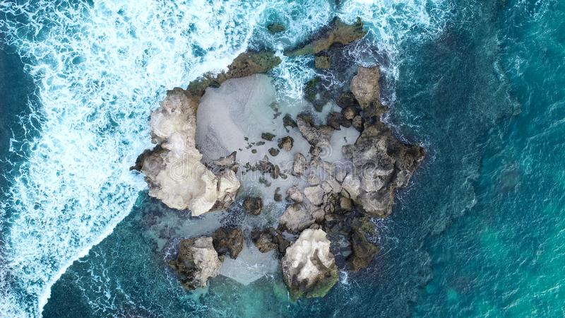 Aerial view of rocky outcrop near coastline showing waves rolling over rocks and sandy middle is home to seal colony royalty free stock images