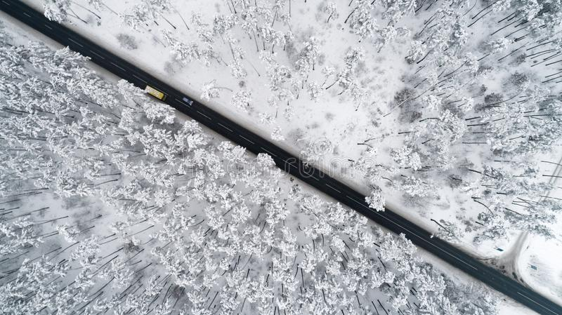 Aerial view of the romantic road passing through the snow-covered winter forest. Top view stock photos