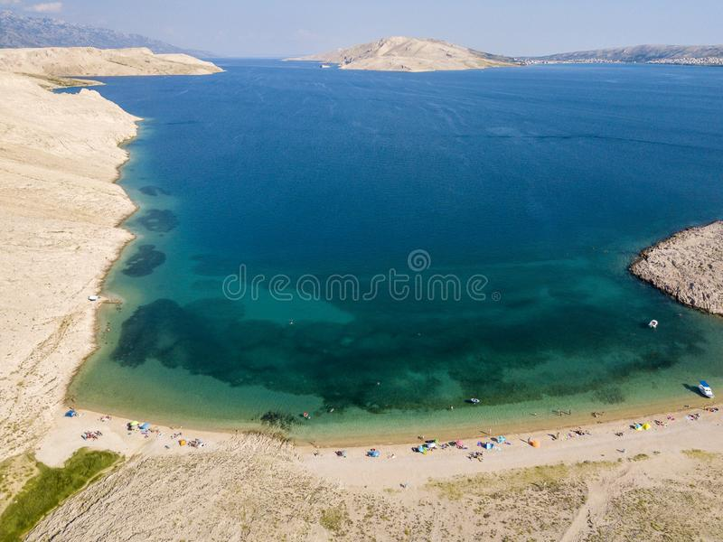 Aerial view of Rucica beach on Pag island, Metajna, Croatia. Seabed and beach seen from above, bathers, relaxation and holidays. Aerial view of Rucica beach on royalty free stock image