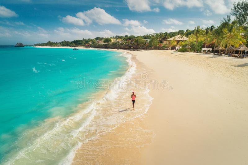 Aerial view of the running young woman on the white sandy beach stock photos