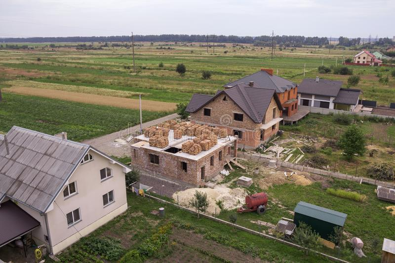 Aerial view of rural land for development in green field. New no. T finished brick houses and building sites on background of distant city and trees on horizon stock photo