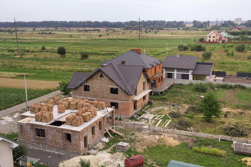 Aerial view of rural land for development in green field. New not finished brick houses and building sites on background of distan. T city and trees on horizon stock photo