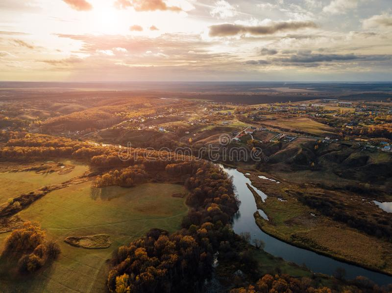 Aerial view of rural landscape in autumn sunset. Small village houses, river, autumn trees, farm fields from drone point of view royalty free stock image