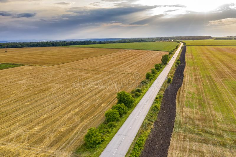 A rural landscape with a farm road, wheat fields after harvest. Aerial view of a rural landscape with a farm road, wheat fields after harvest stock photography