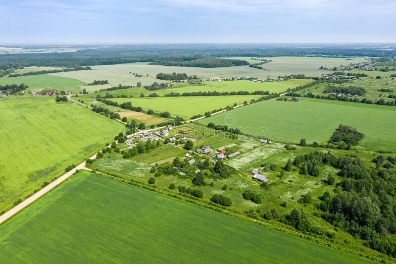 Aerial view of rural village among green fields in sunny summer day royalty free stock image