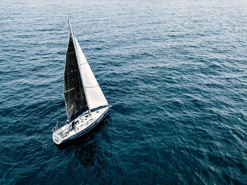 Aerial view of sailing ship yacht with white and black sails at deep open sea. In Italy royalty free stock image