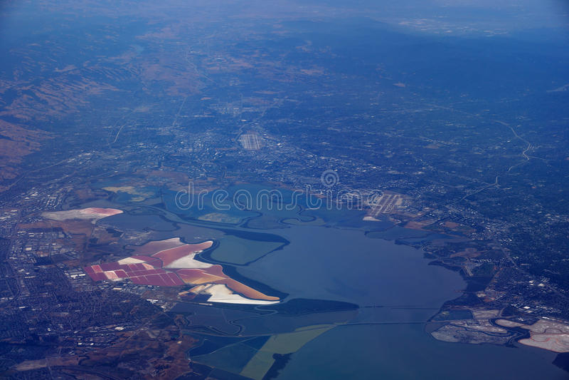 Aerial view of salt evaporation ponds, bridge, airports, cities. Surrounding San Francisco Bay near San Jose, California, United States royalty free stock images
