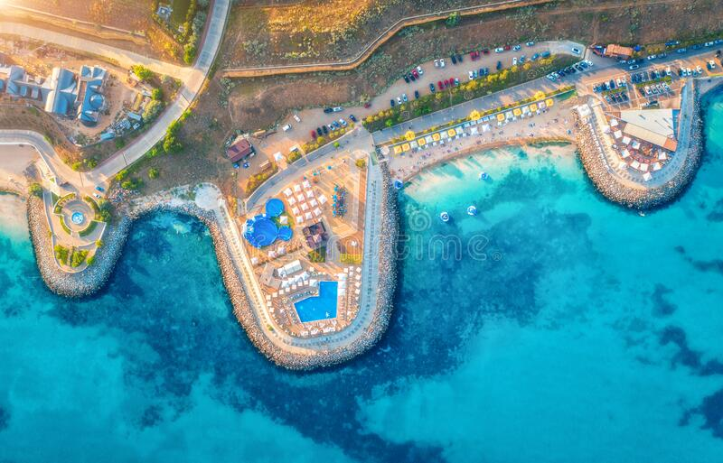Aerial view of sandy beach, blue sea, restaurants at sunset royalty free stock image