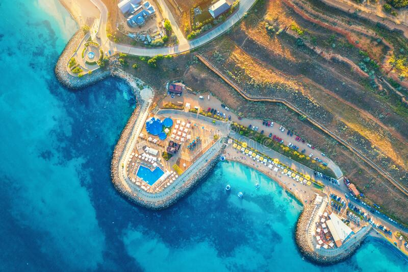 Aerial view of sandy beach, blue sea, restaurants at sunset stock photography