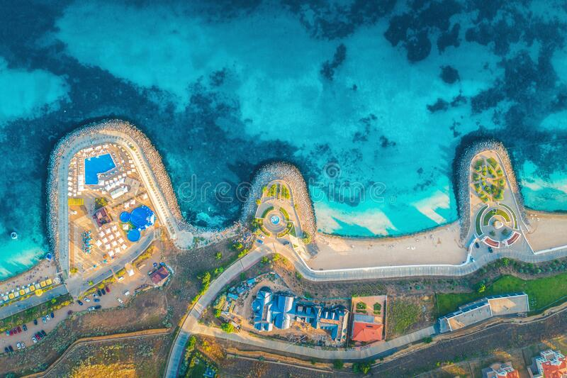 Aerial view of sandy beach, blue sea, restaurants at sunset stock photo