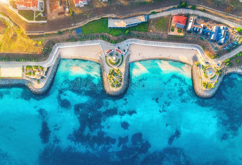 Aerial view of sandy beach, blue sea, restaurants at sunset stock images