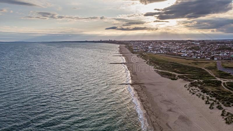 An aerial view of a sandy beach and blue water sea with an urban sea coast area in the background at sunset with ray of light. Across white clouds stock image