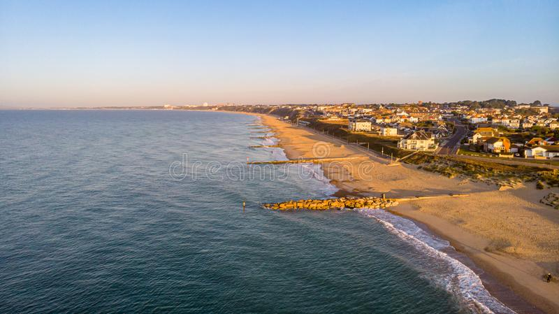 An aerial view of a sandy beach with crystal green water and rocky groyne breakwater along a coastal urban area in the royalty free stock image