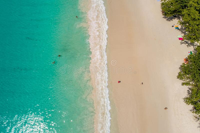 Aerial view of sandy beach with tourists swimming in beautiful clear sea water royalty free stock photo