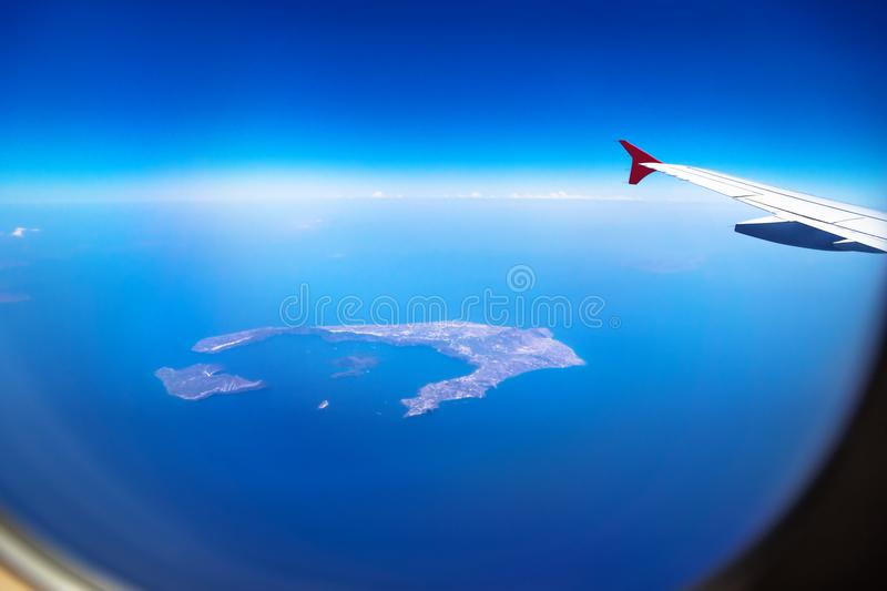 Aerial view from Santorini Island from a plane with window and airplane wing, Santorini, Greece royalty free stock image