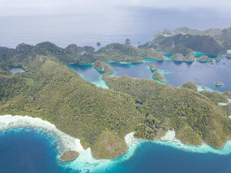 Aerial View of Scenic Rock Islands in Raja Ampat. The scenic limestone islands in Wayag, Raja Ampat, are surrounded by healthy, shallow coral reefs. This remote royalty free stock photo