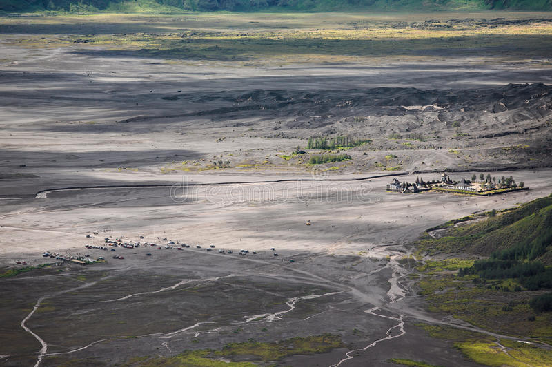 Aerial view of sea of sand inside Bromo Tengger Caldera. Pura Luhur Poten temple and jeep parking royalty free stock photos
