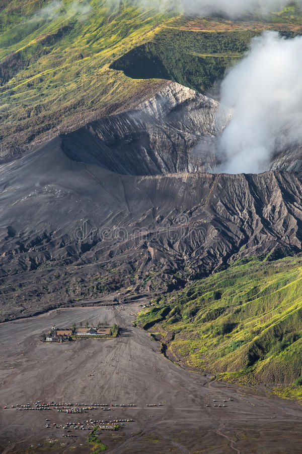 Aerial view of sea of sand inside Bromo Tengger Caldera. Pura Luhur Poten temple and jeep parking stock image