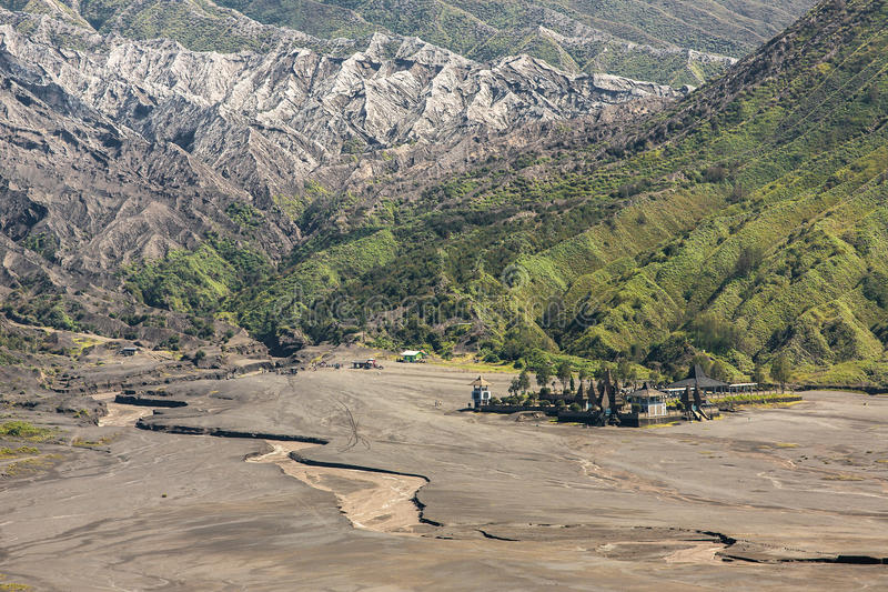 Aerial view of sea of sand inside Bromo Tengger Caldera. Pura Luhur Poten temple and jeep parking royalty free stock photo