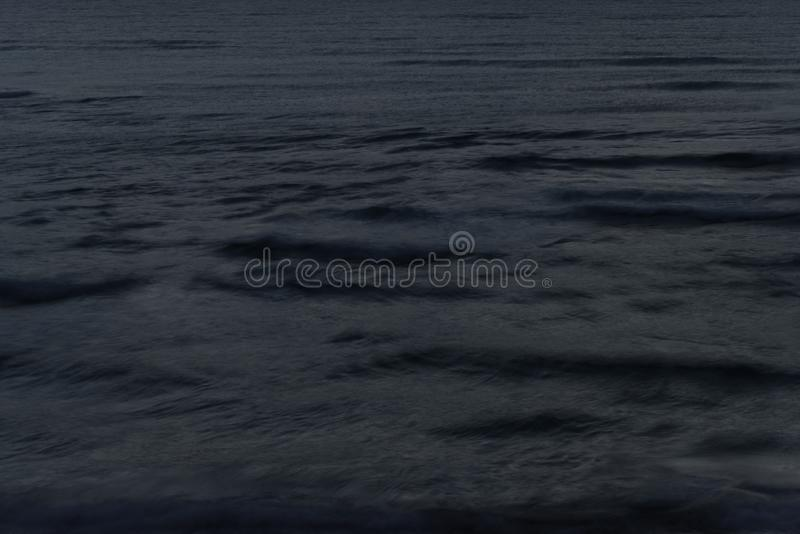 View of the sea wave with a long exposure at night royalty free stock images