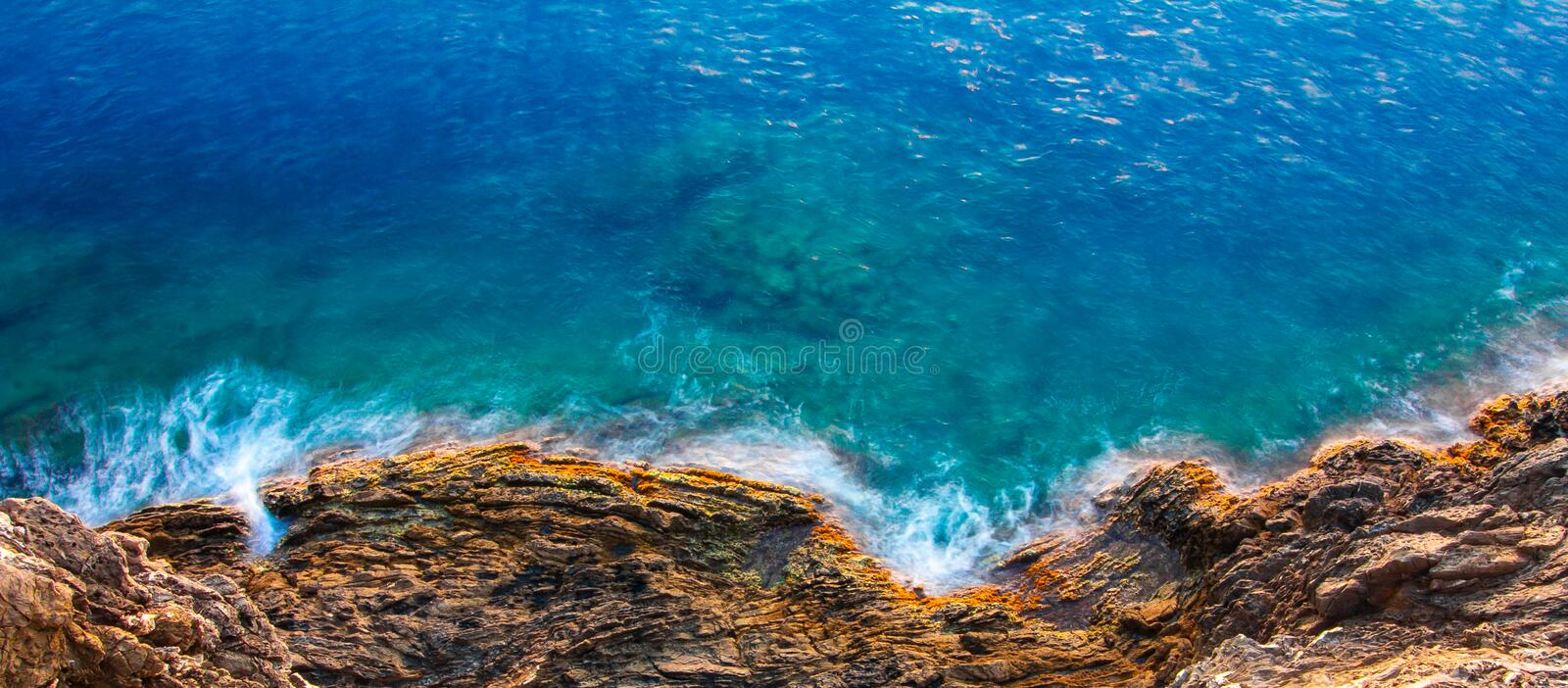 Aerial view of sea waves and rocky coast with turquoise and sapphire clear water. Long exposure royalty free stock photo