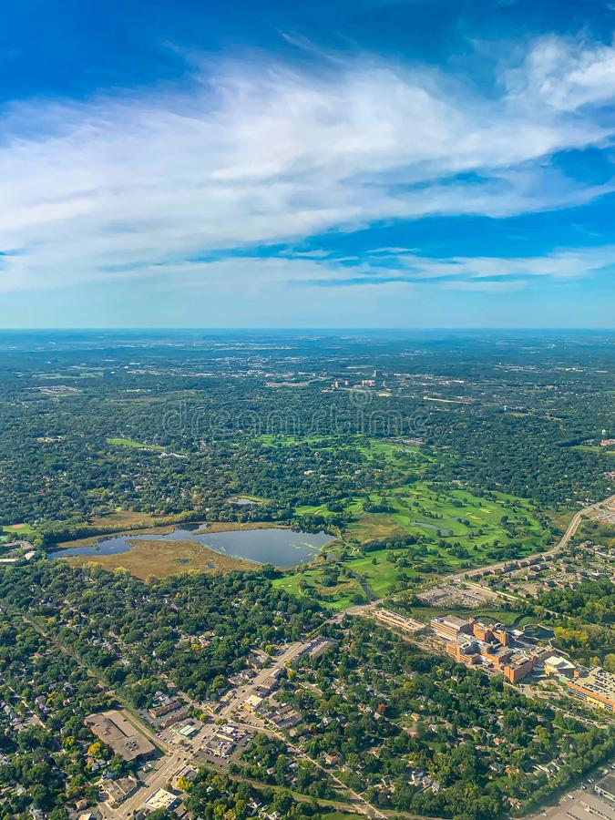 Aerial view of several golf courses in a densely forested urban development royalty free stock images