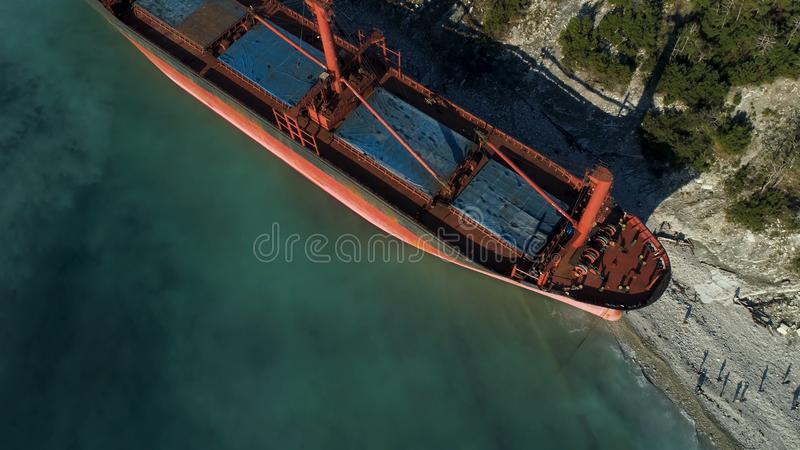 Aerial view of the ship washed ashore. Shot. Top view of an abandoned old and rusty shipwreck on a stormy day.  royalty free stock photos
