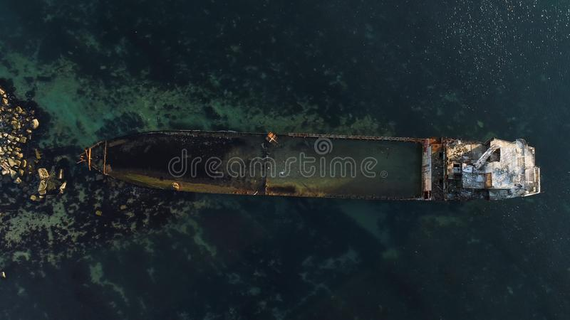 Aerial view of the ship washed ashore. Shot. Top view of an abandoned old and rusty shipwreck on a stormy day.  royalty free stock image