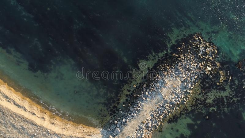 Aerial view of the ship washed ashore. Shot. Top view of an abandoned old and rusty shipwreck on a stormy day.  royalty free stock photo