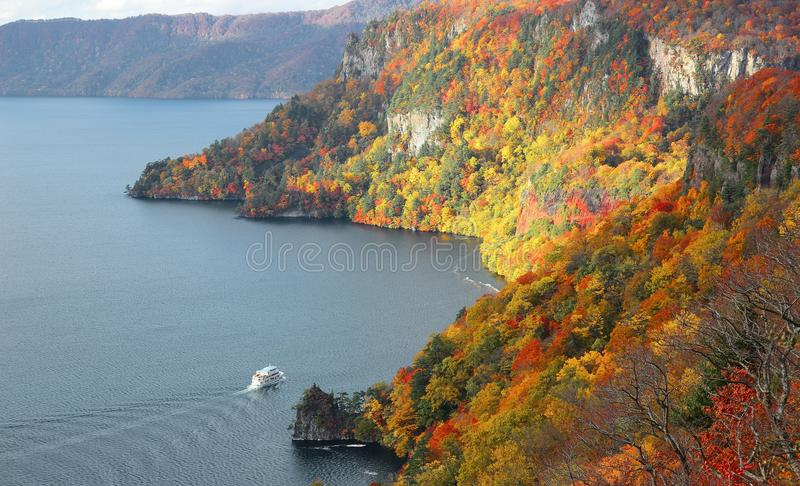 Aerial view of a sightseeing boat on autumn Lake Towada, in Towada Hachimantai National Park, Aomori, Japan. Lake Towada is the largest crater lake in Honsh royalty free stock photography