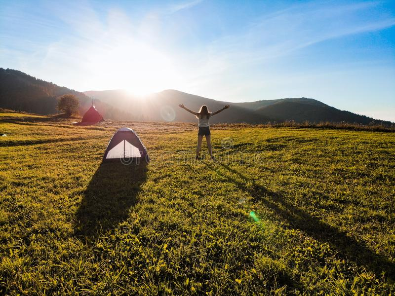 Aerial view of silhouette young woman with raised hands standing on meadow and admire beautiful mountains sunset stock photography