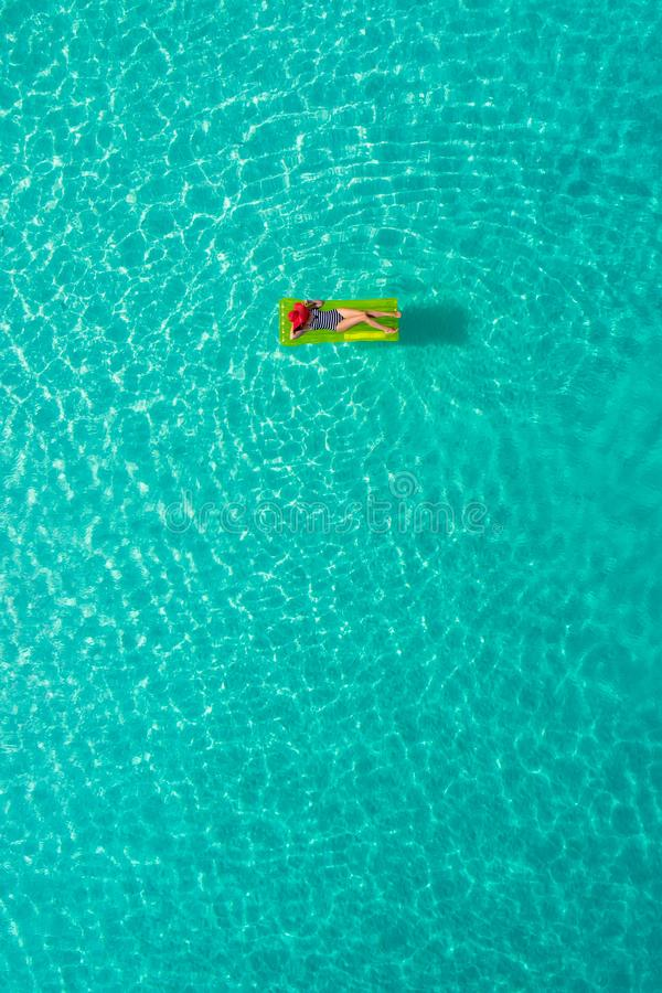 Aerial view of slim woman swimming on the swim mattress in the transparent turquoise sea in Seychelles. Summer seascape with girl. Beautiful waves, colorful stock photography