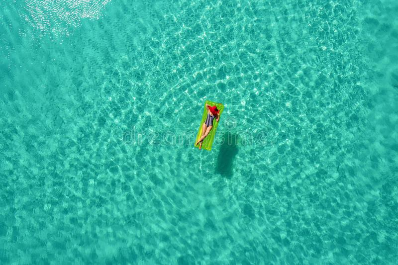 Aerial view of slim woman swimming on the swim mattress in the transparent turquoise sea in Seychelles. Summer seascape with girl. Beautiful waves, colorful stock photos